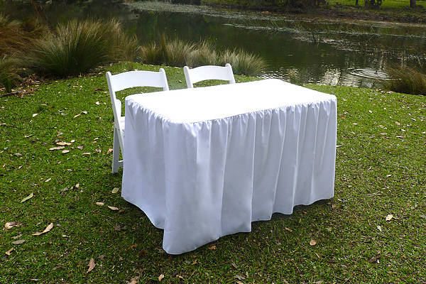 Signing Table with White Cloth and Two White Folded Chairs